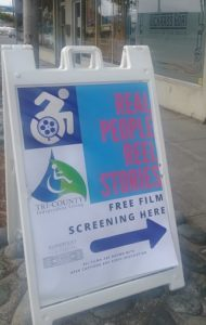 A sandwich sign on the sidewalk shows with an arrow where the film screening event will take place